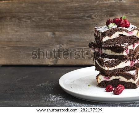Brownies-cheesecake tower with raspberries on white ceramic plate, wooden backdrop, copy space - stock photo