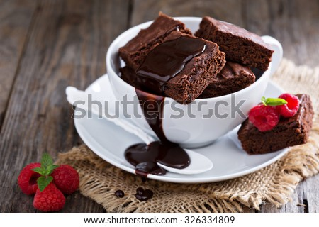 Brownies in stacked coffee cups with hot fudge chocolate sauce - stock photo