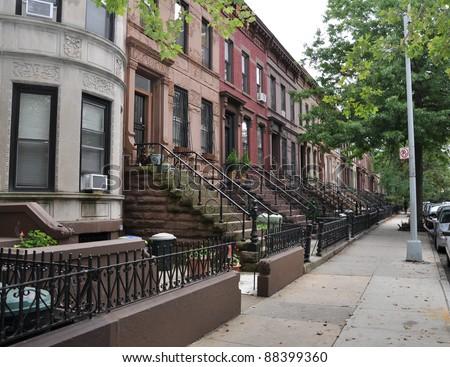 Brownstone Homes along residential Neighborhood sidewalk in Brooklyn New York on overcast sky day - stock photo