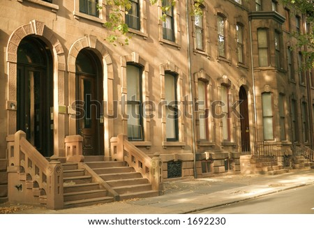 Brownstone row houses on a residential street.