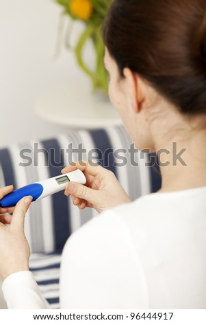 Bruenette woman with pregnancy test at home - stock photo