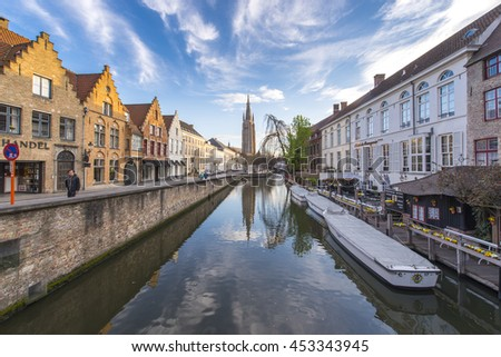 BRUGES, BELGIUM - APRIL 12: Panorama view of canal, colorful traditional houses and church of our lady against cloudy blue sky in Bruges, Belguim on April 12, 2016. - stock photo
