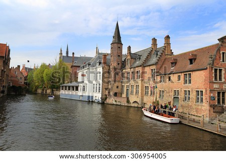 Bruges, Belgium, April 16, 2015. Tourists on a canal boat tour