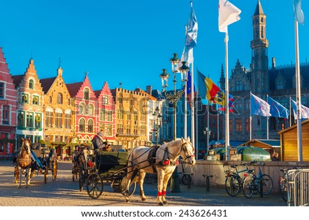 Bruges, Belgium - December 28, 2014: Horse carriage waiting tourists at Christmas morning on Grote Markt square of Brugge. Belgian city of Bruges is UNESCO world heritage listed for its medieval - stock photo