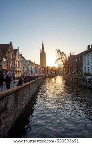 BRUGES, BELGIUM - DECEMBER 3, 2016: Sunset over the canals of Bruges, some people walk on the street, some take a rest on benches.
