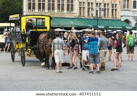 BRUGES, BELGIUM - JULY 3, 2015: A group of tourists having fun near a buggy, in one of the squares of the historic town. - stock photo