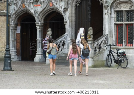 BRUGES, BELGIUM - JULY 3, 2015: A young girls walking in one of the squares of the historic town.