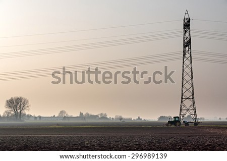 BRUGES, BELGIUM - March 16, 2011: A tractor parked on a agricultural field just near an electricity pylon. - stock photo