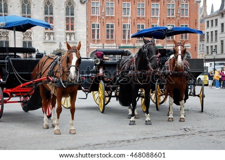 BRUGES, BELGIUM - SEPT 21, 2011 - Horse-driven cabs with four wheel horse carriages.This is one of the main tourist attractions in the commercial heart of medieval-looking city of Bruges , Belgium