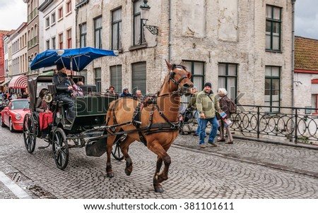 BRUGES (BRUGGE), BELGIUM - 2015 APR 28: Horse-driven cab on the bridge in Brugge - running horse hitched to a four wheel horse carriage. This is the main tourist attraction (focus with panning).