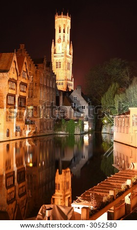 Bruges by night (Belgium). Old houses near the waterfront with belfry tower at the background. - stock photo