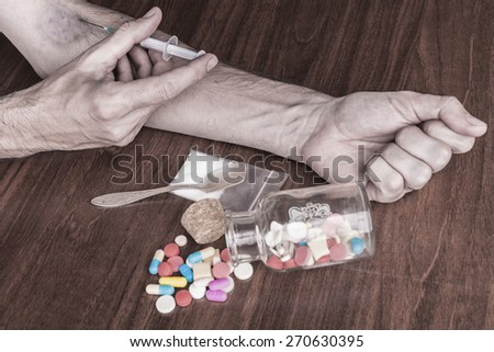 Bruised hand with needle and pills on the table  - stock photo