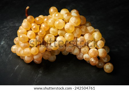 Brunch of ripe and juicy green grapes on a black background. - stock photo