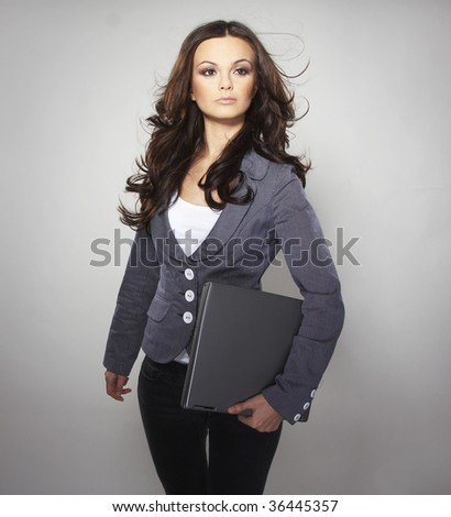 Brunet Business woman standing  with gray laptop on light backgroung - stock photo
