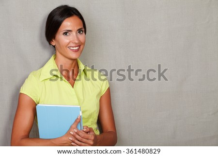 Brunette adult female carrying mobile technology and smiling with toothy smile while holding tablet and looking at camera against grey texture background