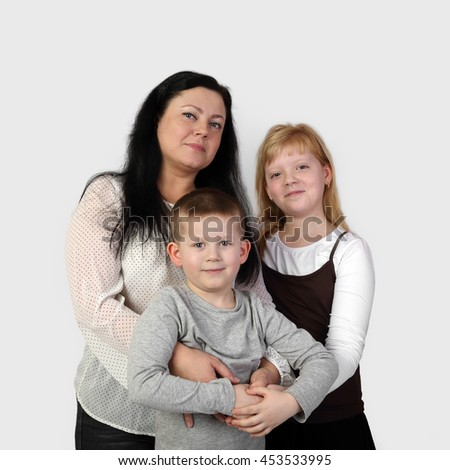 Brunette adult woman and teenage blonde girl embrace little boy smiling on gray background in square - mother, son and daughter - family relations and love concept - stock photo