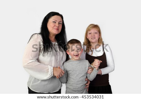 Brunette adult woman and teenage blonde girl hold smiling little toothless boy hands on gray background - mother, son and daughter - family relations and love concept - stock photo