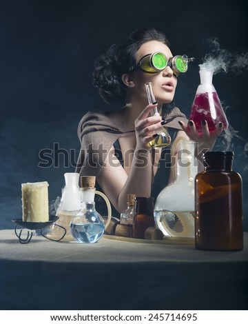 brunette alchemist girl th test tubes in hand on a gray background