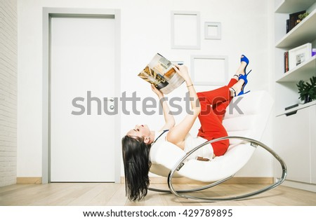 brunette asian Woman relaxing in armchair near door and white wall, reading magazine, smiling, serious face. young adult girl wear red  trousers and blue high heel - stock photo