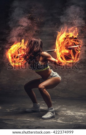 Brunette athletic female doing squats with burn barbell on her shoulders. - stock photo