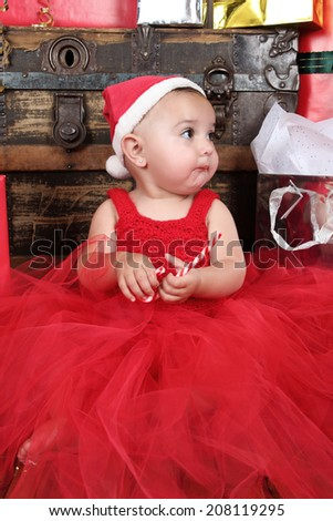 Brunette baby girl wearing a red christmas dress eating candy - stock photo