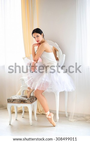 Brunette ballerina in room, wearing  costume, ballet skirt and corset. - stock photo