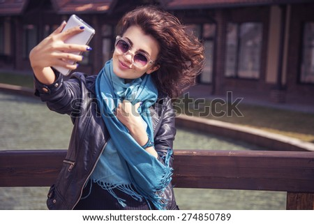Brunette beautiful stylish caucasian woman in casual outfit on a walk on european city street making selfie on her phone. copy space - stock photo