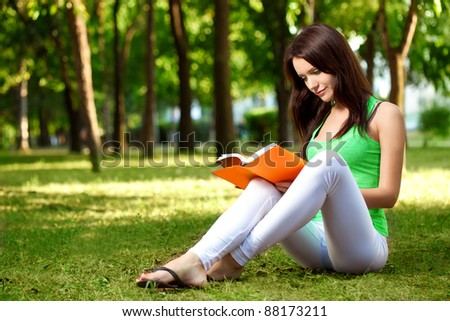 brunette beautiful woman sitting on ground and reading book