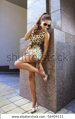brunette beautiful woman stands near wall of building - stock photo