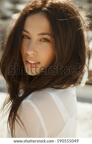 Brunette beauty. attractive woman with long hair. vertical shot, outdoors - stock photo