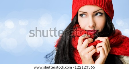 Brunette beauty in winter fashion on blue background with white glow circle pattern. - stock photo