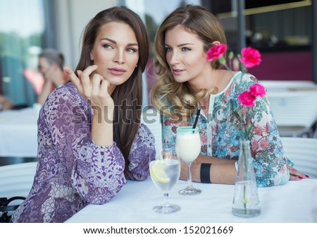 Brunette beauty showing something her best friend - stock photo