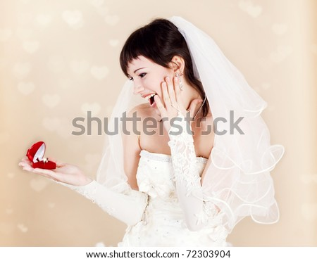 Brunette bride looking at the wedding ring - stock photo