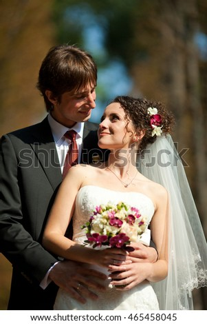 Brunette bride looks at a groom leaning to his shoulder