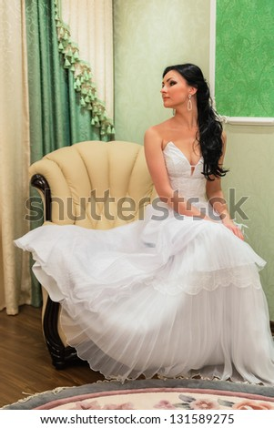 Brunette bride sitting on the armchair in room - stock photo