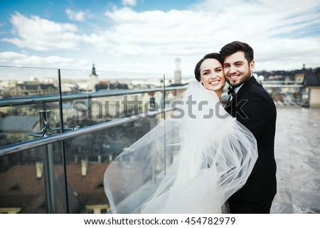Brunette brunette bride and bridegroom standing close to each other at old city background and smiling, wedding photo, looking at camera. - stock photo