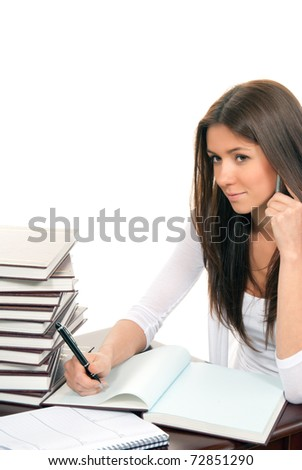 Brunette Business woman sitting in an office writing and talking on mobile phone with a pen in the hand offer to sign contract, on the table books, paper and notebook isolated on a white background - stock photo