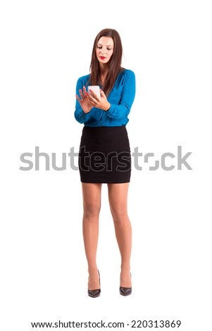Brunette business woman using touch screen on her smart phone. Full body length isolated over white background. - stock photo