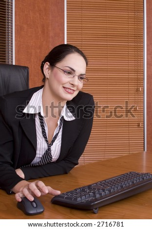 Brunette business woman with black suit working with mouse