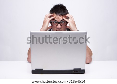 Brunette businessman looks at his computer in disbelief isolated on white - stock photo