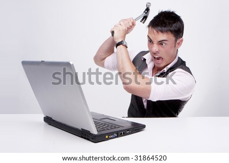 Brunette businessman looks at his computer in disbelief killing his computer using a hammer - stock photo