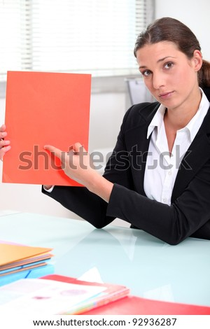 Brunette businesswoman pointing to a file left blank for your image - stock photo