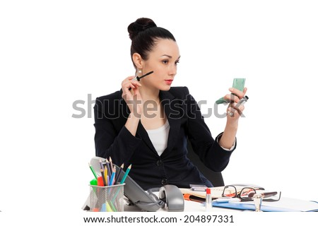 brunette businesswoman putting on her make-up at work over white background  - stock photo