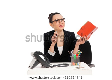 brunette businesswoman sitting in office chair and writing in notebook over white background  - stock photo