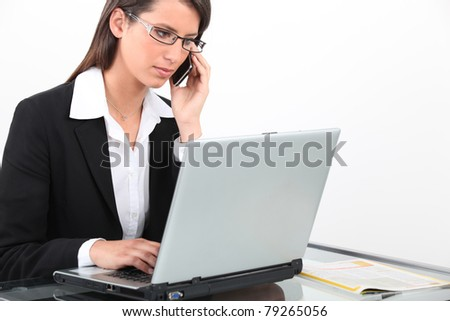 Brunette businesswoman using laptop and mobile telephone - stock photo