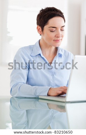 Brunette businesswoman with a laptop in an office - stock photo