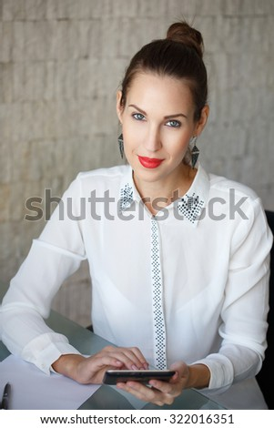 Brunette businesswoman working on tablet in office - stock photo