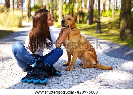 Brunette casual female having fun with her brown pitbull dog in a park. - stock photo