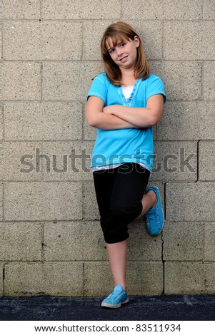 Brunette caucasian cute girl in turquoise blouse and shoes leaning against cinder block wall - stock photo