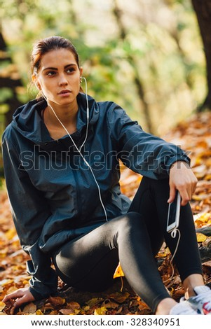 brunette caucasian runner woman rest on the leaves in park, listening music, closeup view - stock photo